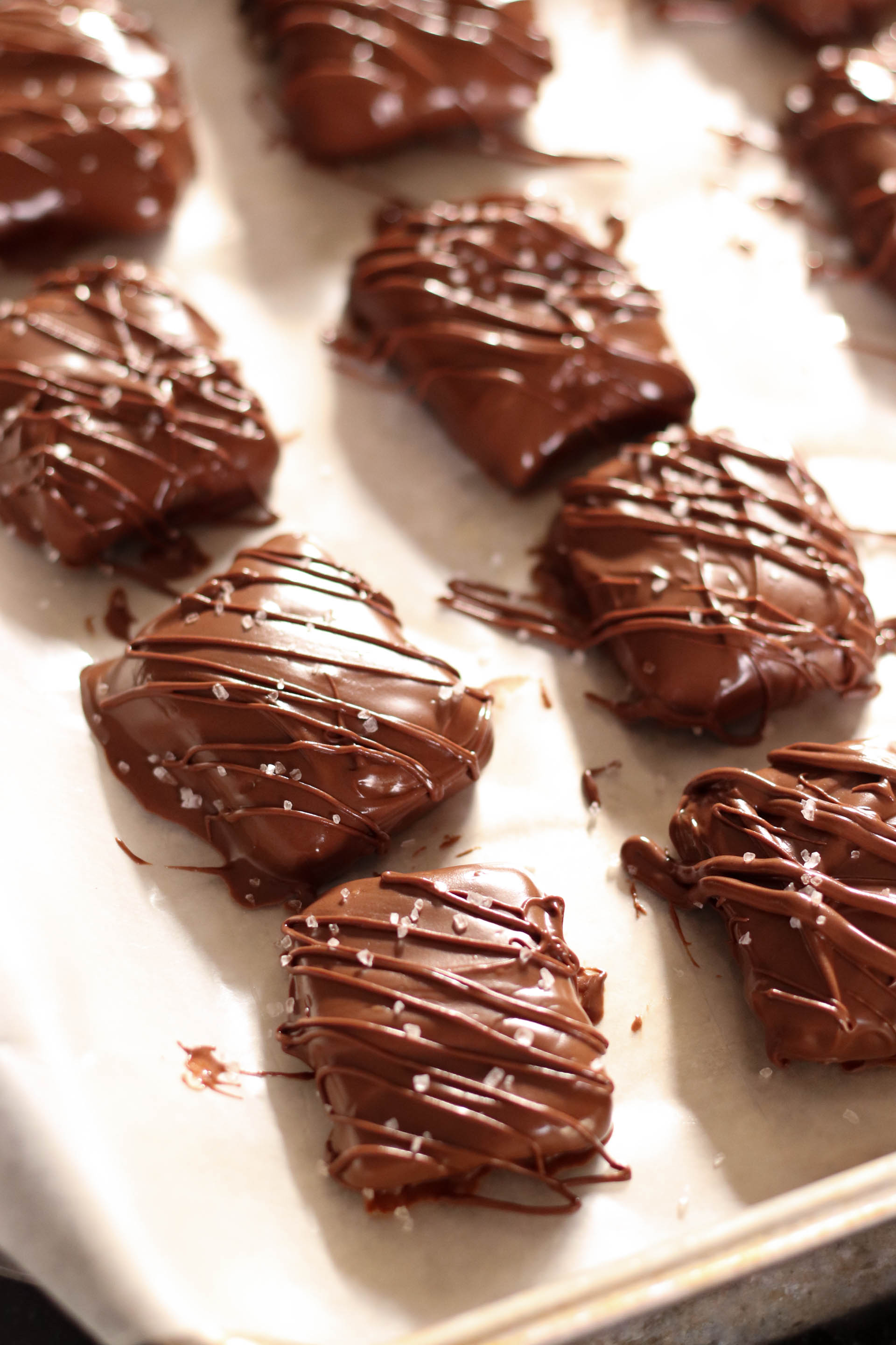 milk chocolate caramels with drizzled chocolate on top sprinkled salt on top