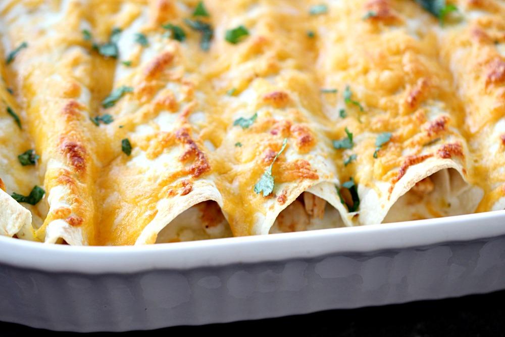 Honey Lime Chicken Enchiladas in white casserole dish