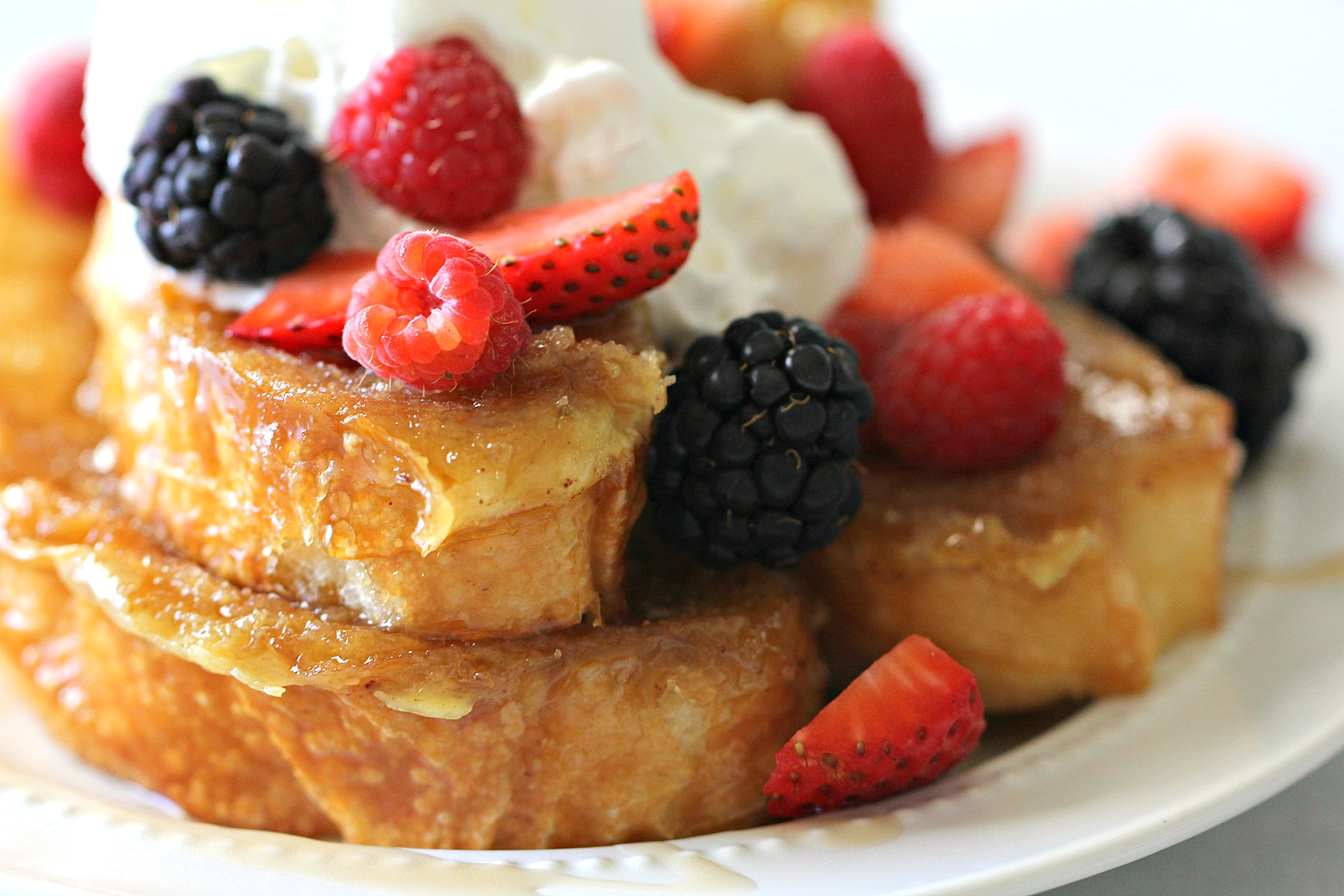 close up of caramelized french toast topped with berries and whipped cream