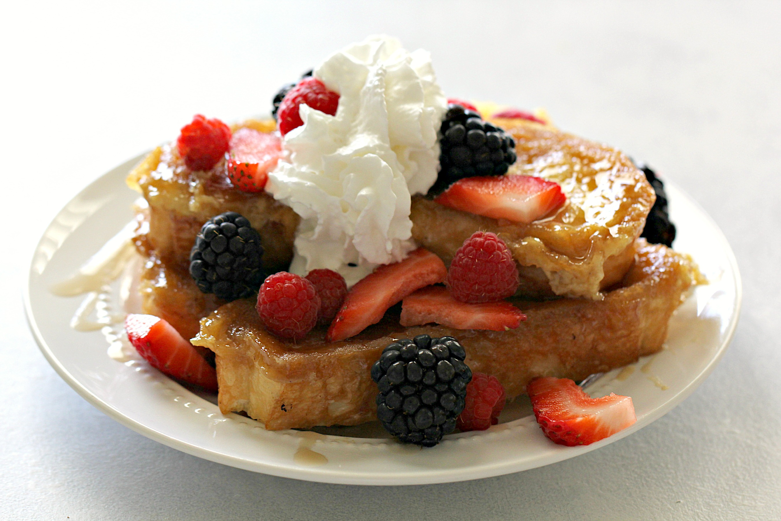 stack of creme brulee french toast topped with raspberries, strawberries, blackberries, and whipped cream