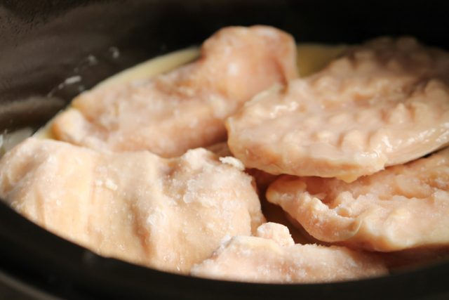 frozen chicken breasts placed in a slow cooker
