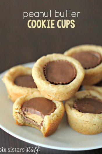 peanut butter cookies stacked on a plate with peanut butter cup in the middle of them