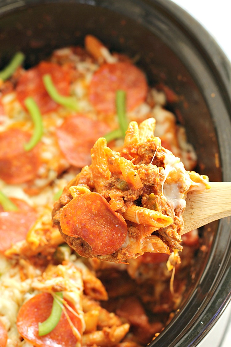 Slow Cooker Pizza Pasta Bake in a slow cooker with a wooden spoon