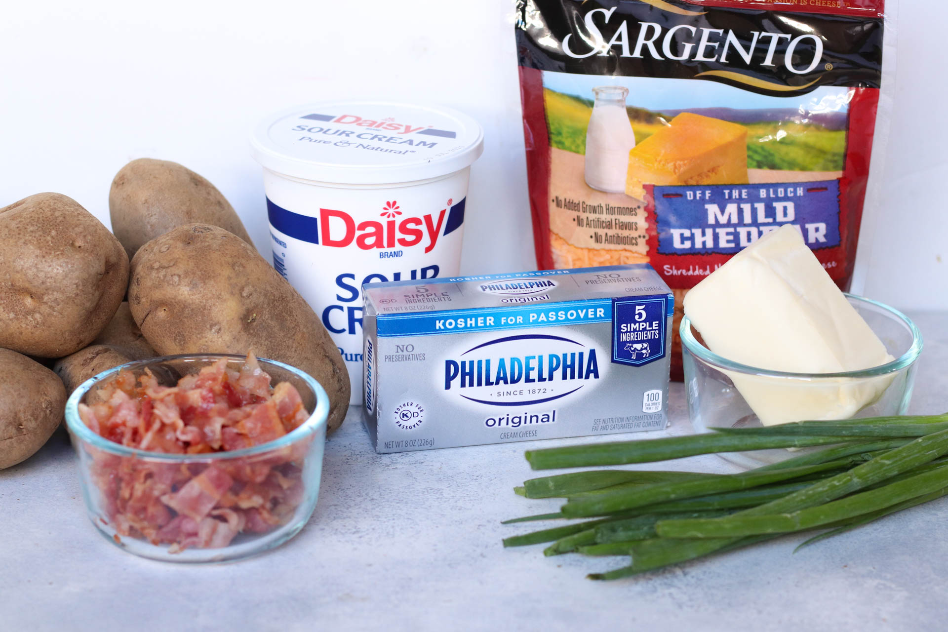 Ingredients for this recipe including potatoes, bacon, sour cream, cream cheese, butter, green onions, cheddar cheese