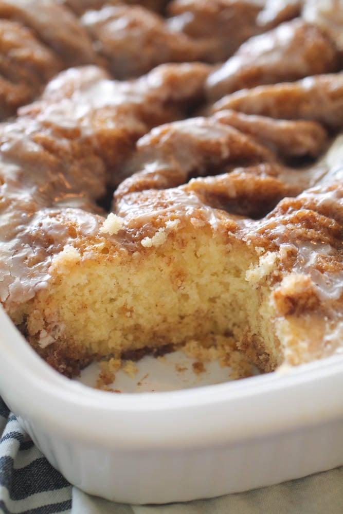 Cinnabon Cinnamon Roll Cake in cake pan with one corner slice missing