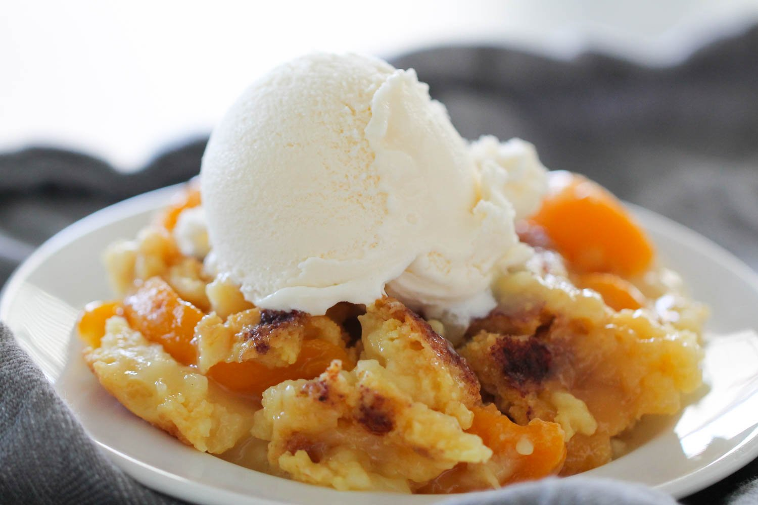 Peach Cobbler Dump Cake topped with ice cream on white plate