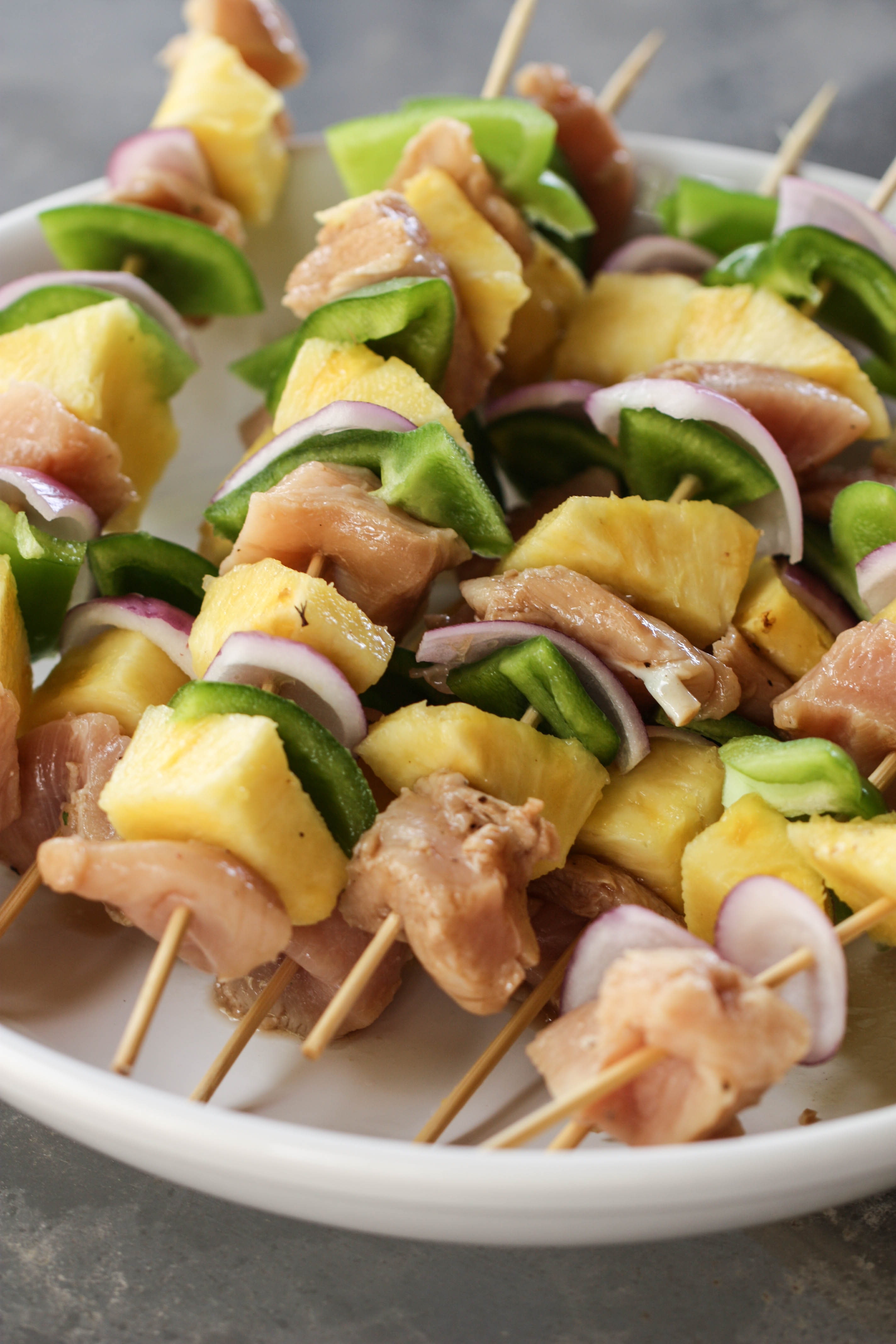 Raw Grilled Island Chicken Kabobs on a white plate
