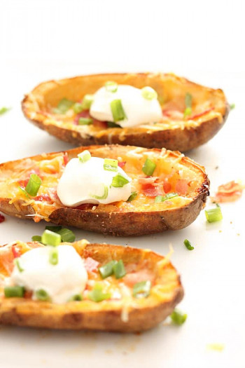 Loaded Baked Potato Skins plated and ready to eat with a dollop of sour cream on top