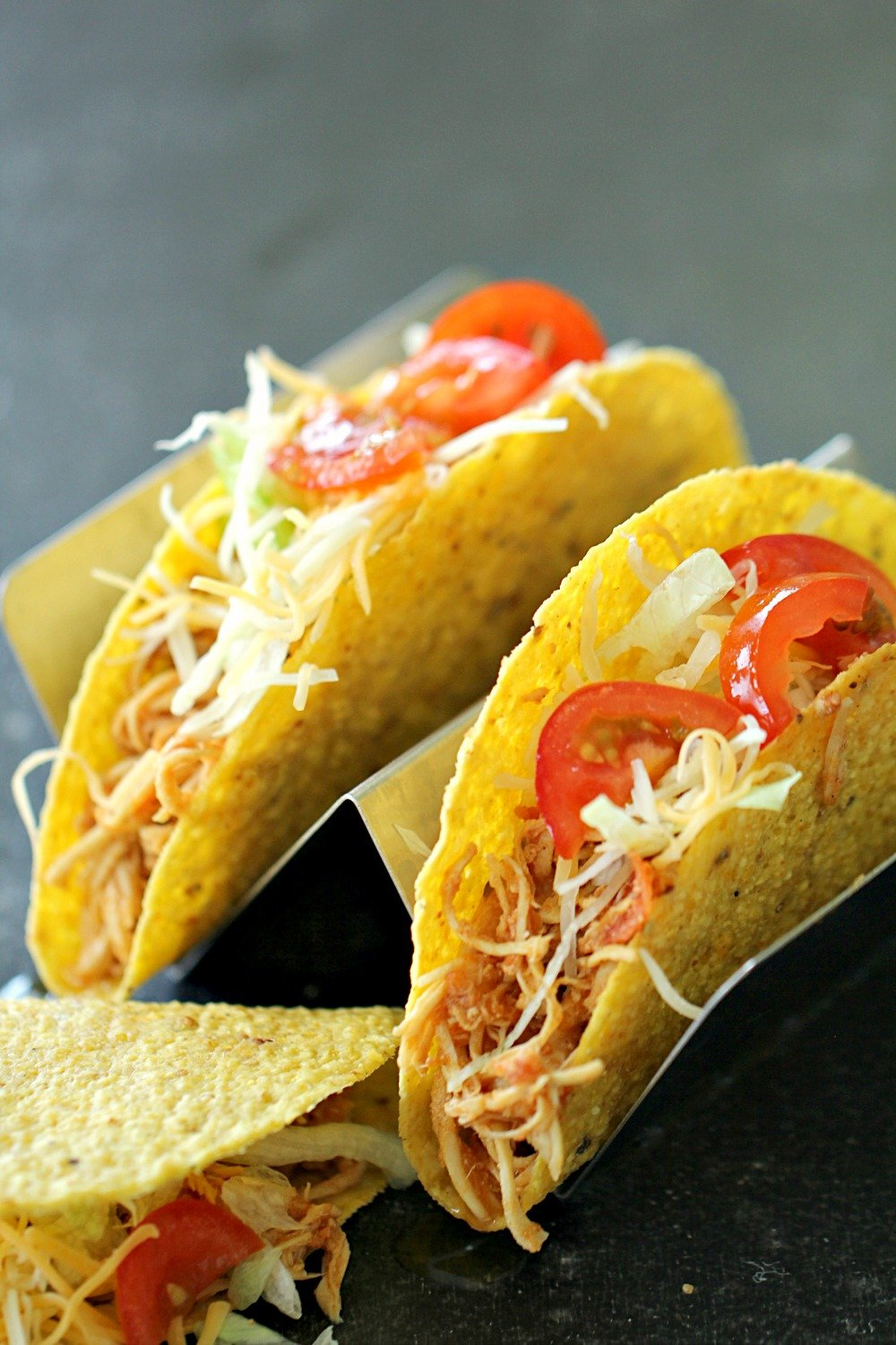 3 Ingredient Slow Cooker Chicken Tacos in hard taco shells topped with cheese and tomatoes