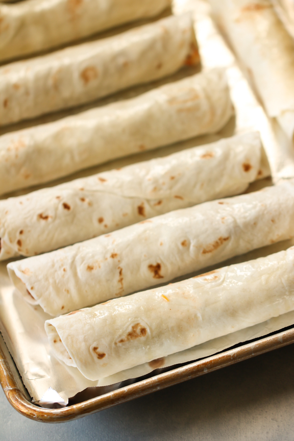 Unbaked Beef Taquitos on a baking sheet covered with foil