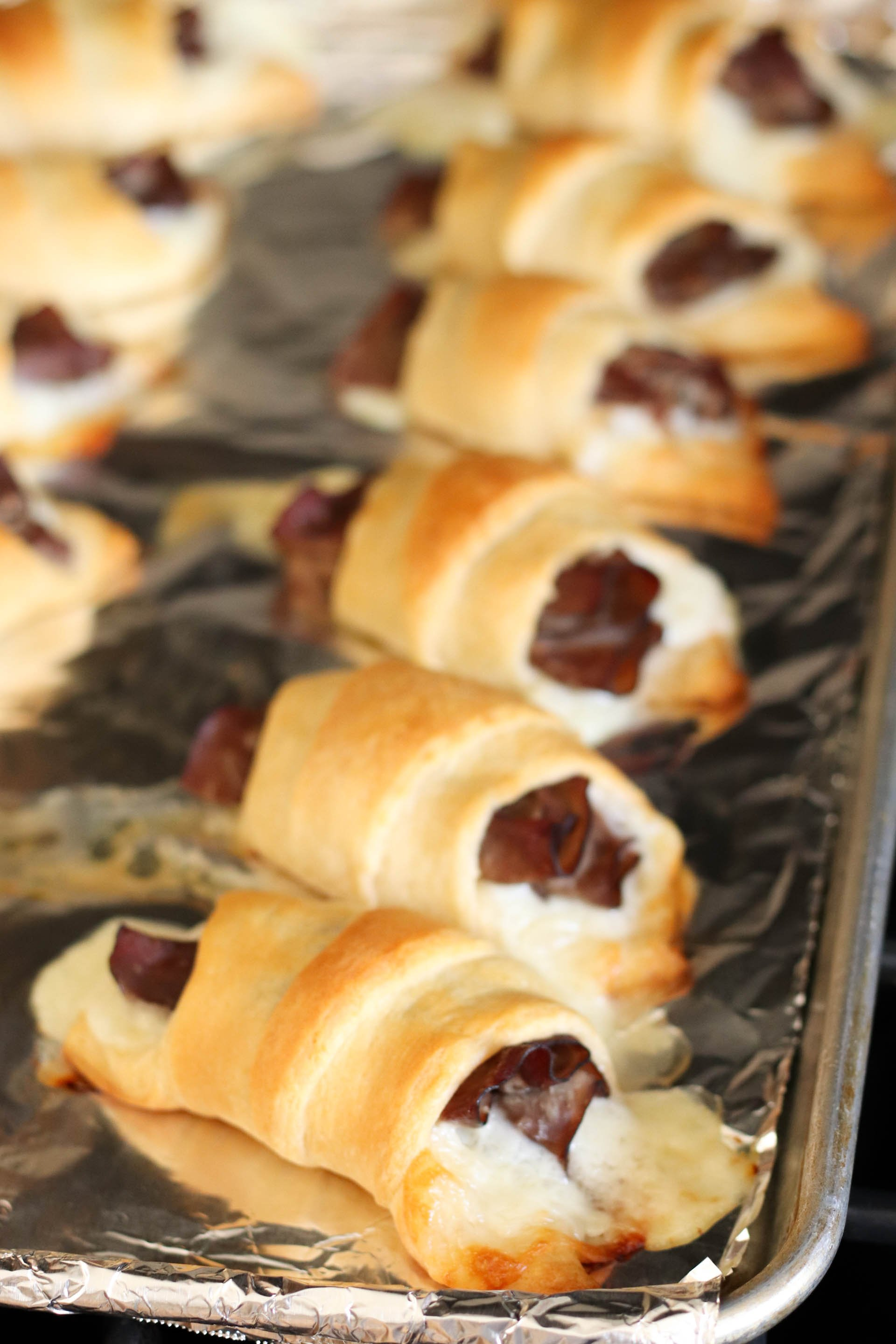 cooked french dip crescents on a foil-lined cookie sheet