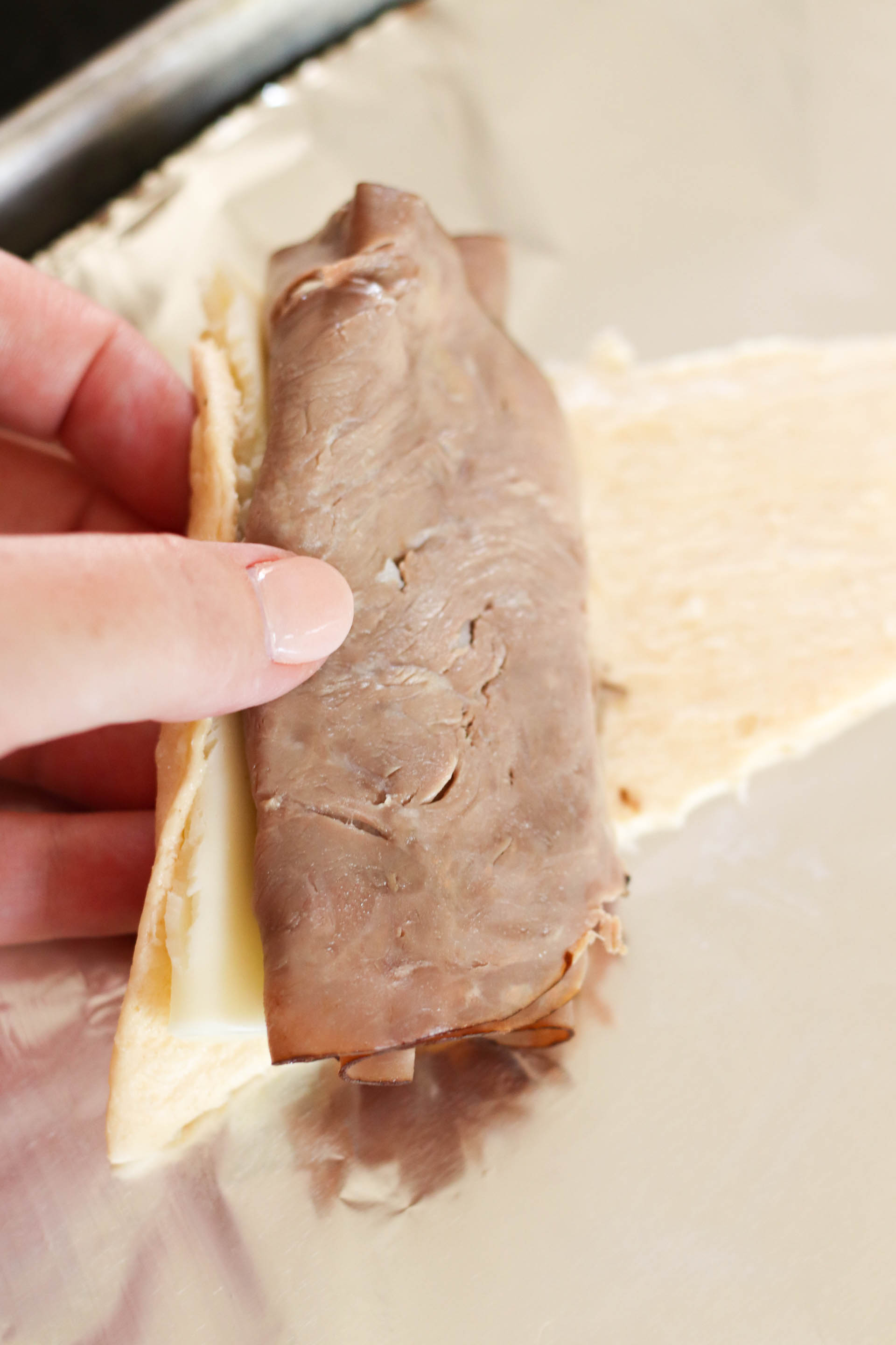 Slice of roast beef and cheese on a spread out crescent, waiting to be rolled up