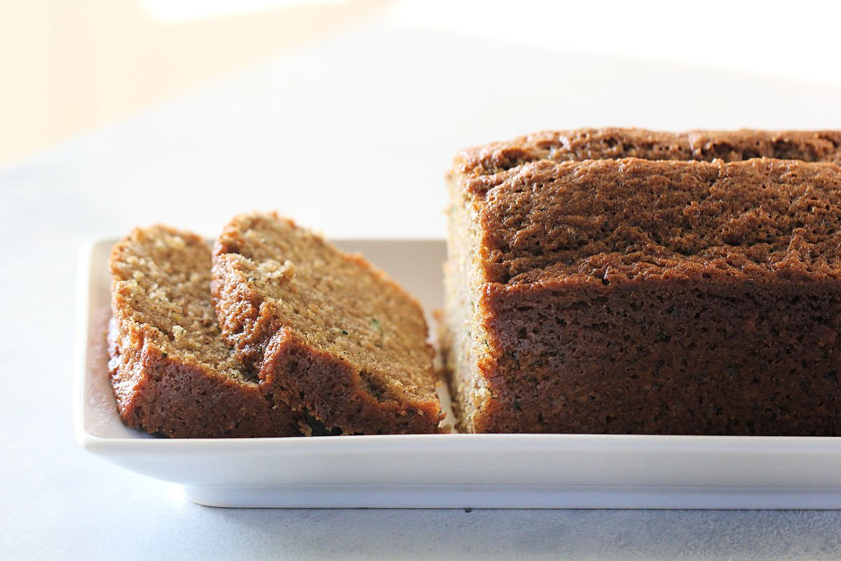 The Best Zucchini Bread Recipe on a white serving plate sliced
