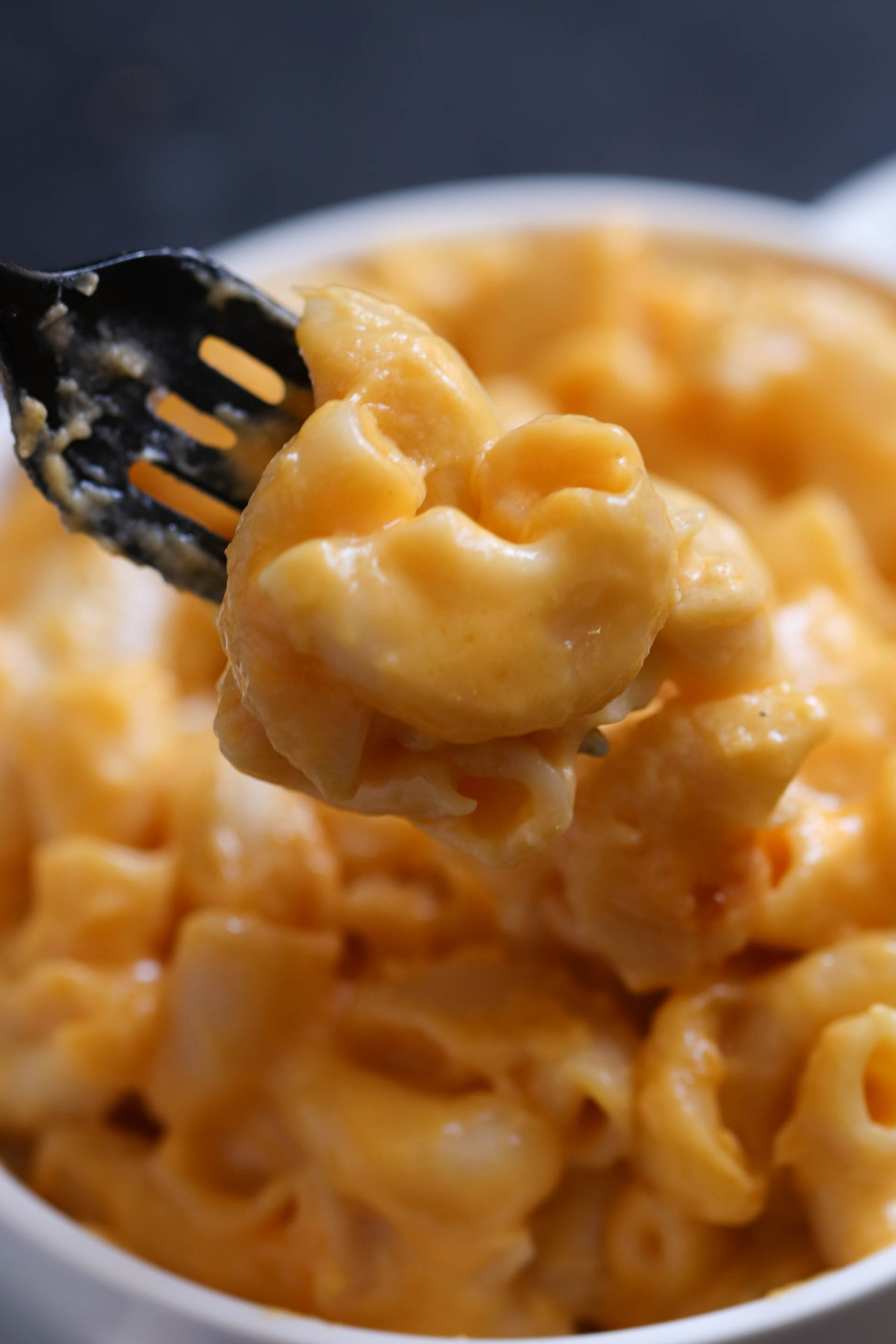 cheesy macaroni and cheese bite with a fork