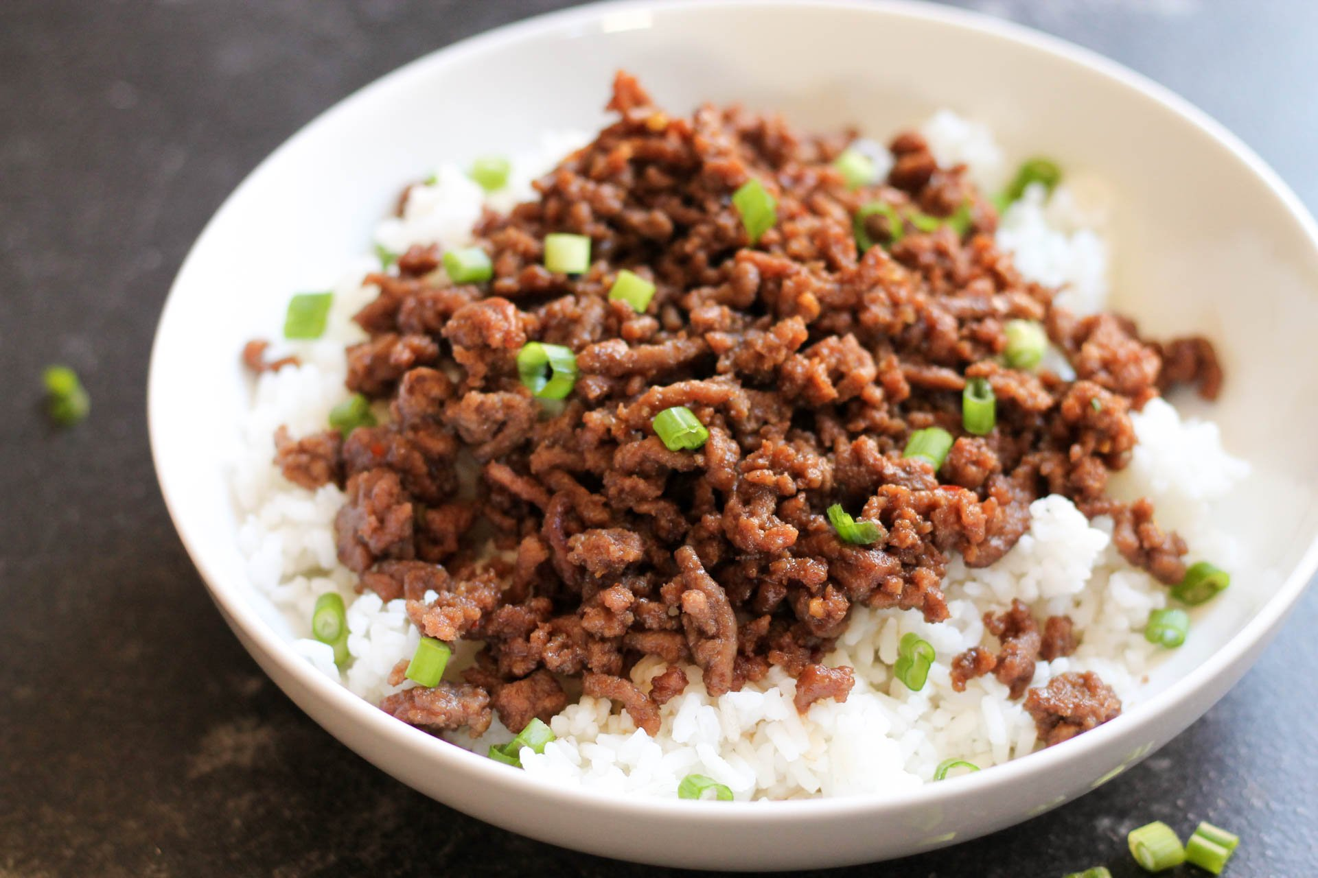 Korean Beef served over white rice in a white bowl