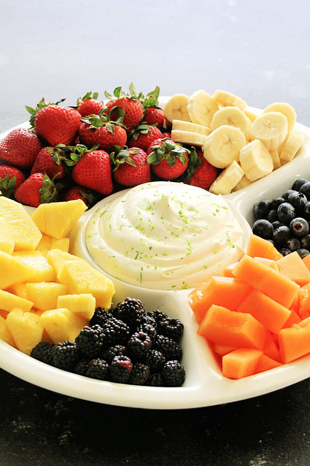 Creamy Lime Fruit Dip served with fruit on a white platter