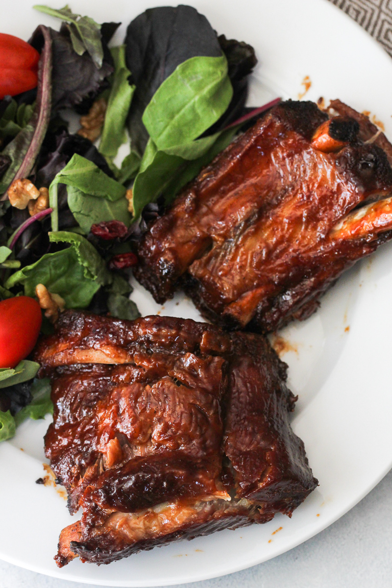 Fall Off The Bone BBQ Ribs on a white plate served with salad