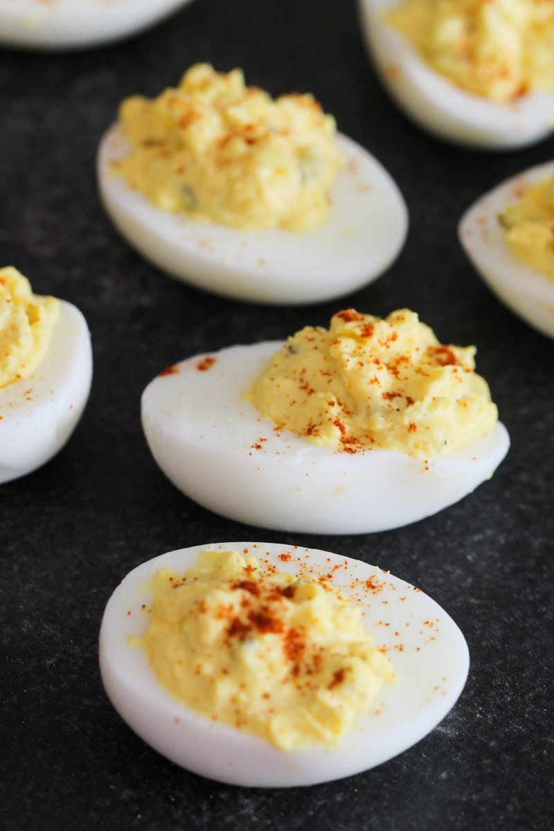 deviled eggs with paprika on top on a black table