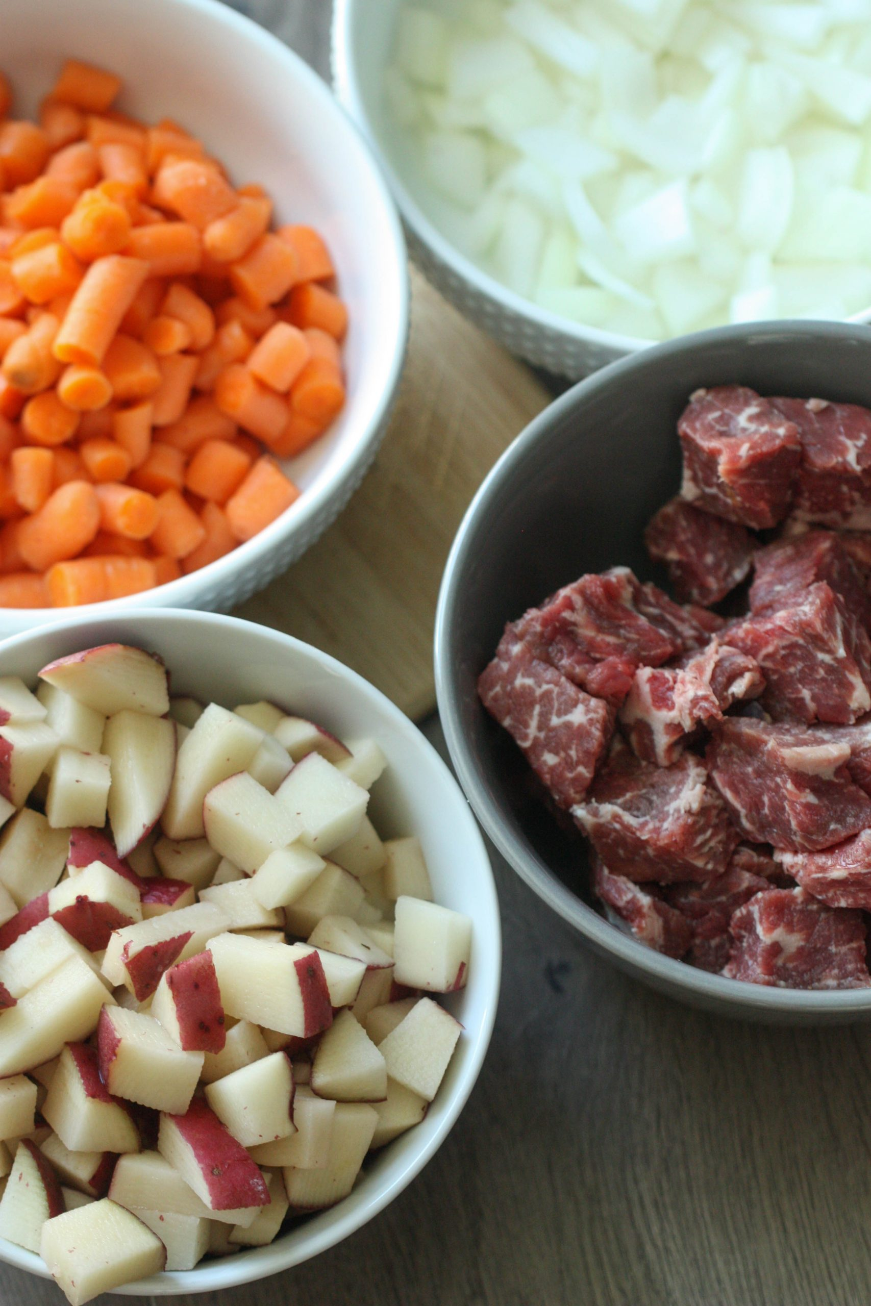 diced meat, carrots, onions and potatoes in bowls
