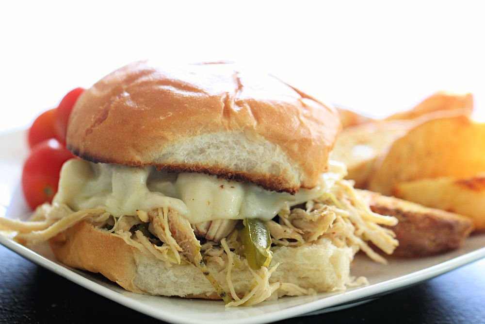 Slow Cooker Chicken Philly Cheesesteak Sandwich on a white plate with chips