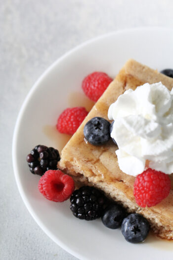 baked pancakes with whipped cream and berries on top
