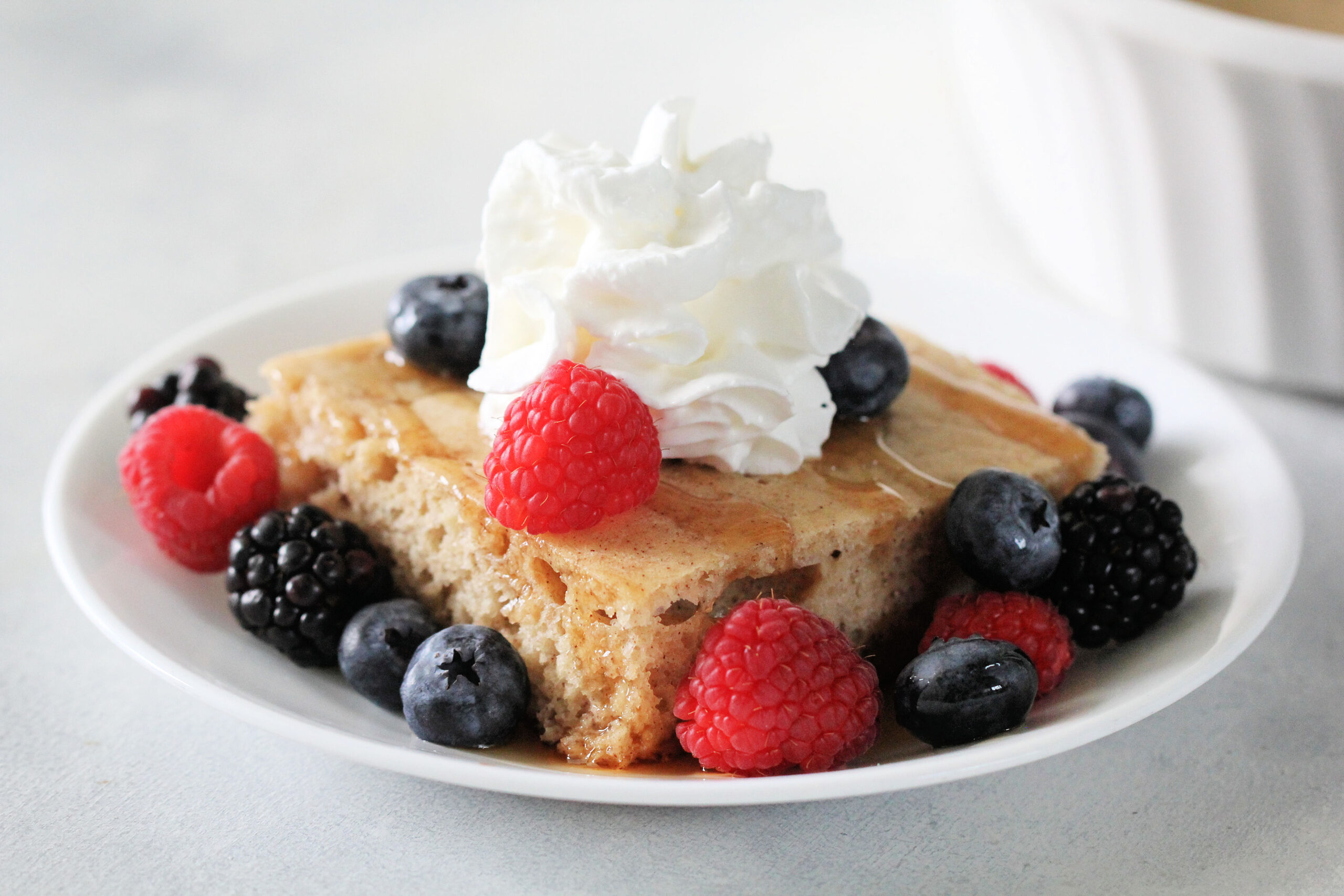 Baked Pancake on white dish with berries and whip cream