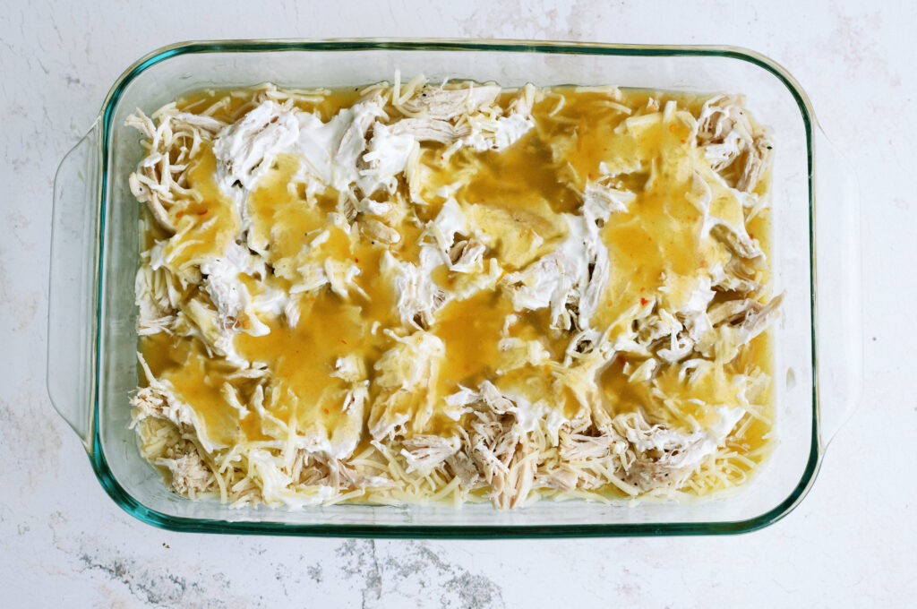 green enchilada sauce on top of the layered enchilada casserole