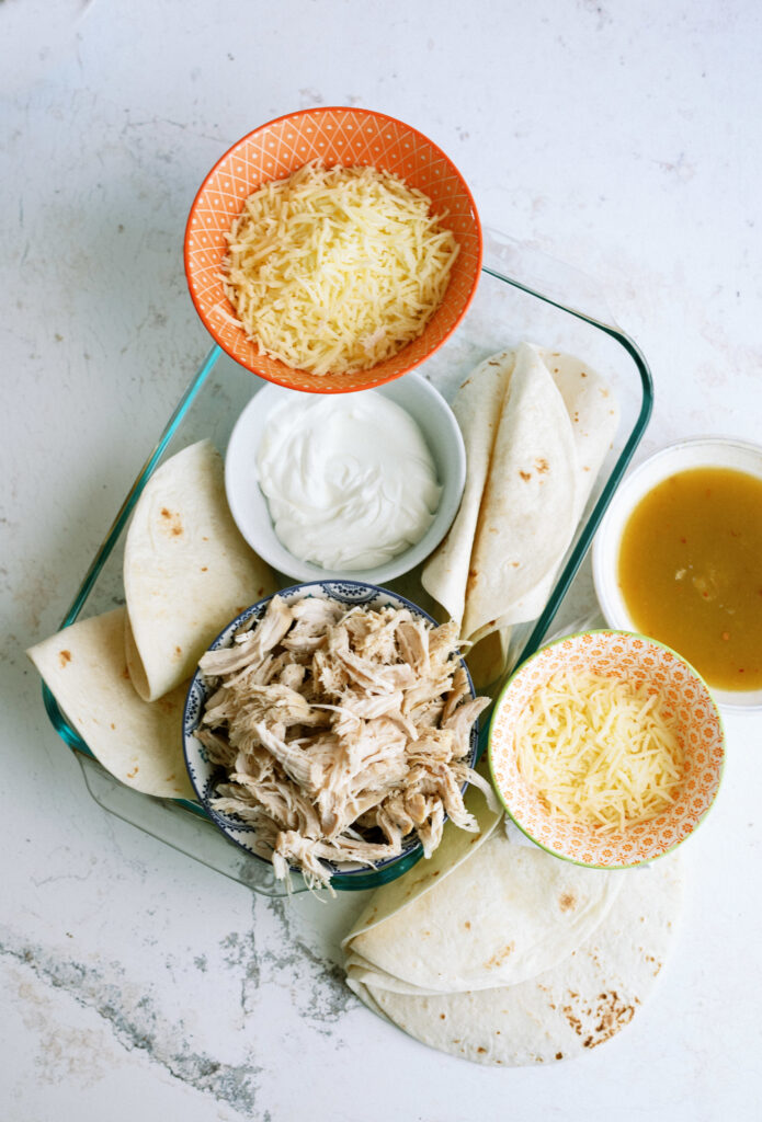 the raw ingredients needed to make this dish: cheese, sour cream, tortillas, green enchilada sauce, cooked chicken