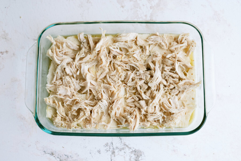 layers of green enchilada sauce, tortillas, and shredded chicken