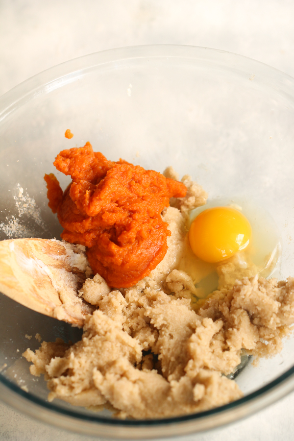 Pumpkin, Egg and Cookie dough together in a glass bowl with a wooden spoon