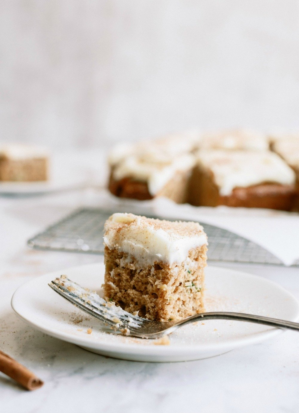 Slice of Cinnamon Zucchini Cake with Cream Cheese Frosting on a plate with fork