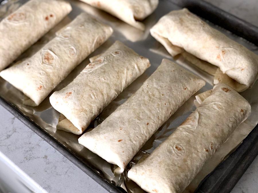 Unbaked Sweet Pork Chimichangas on a baking sheet