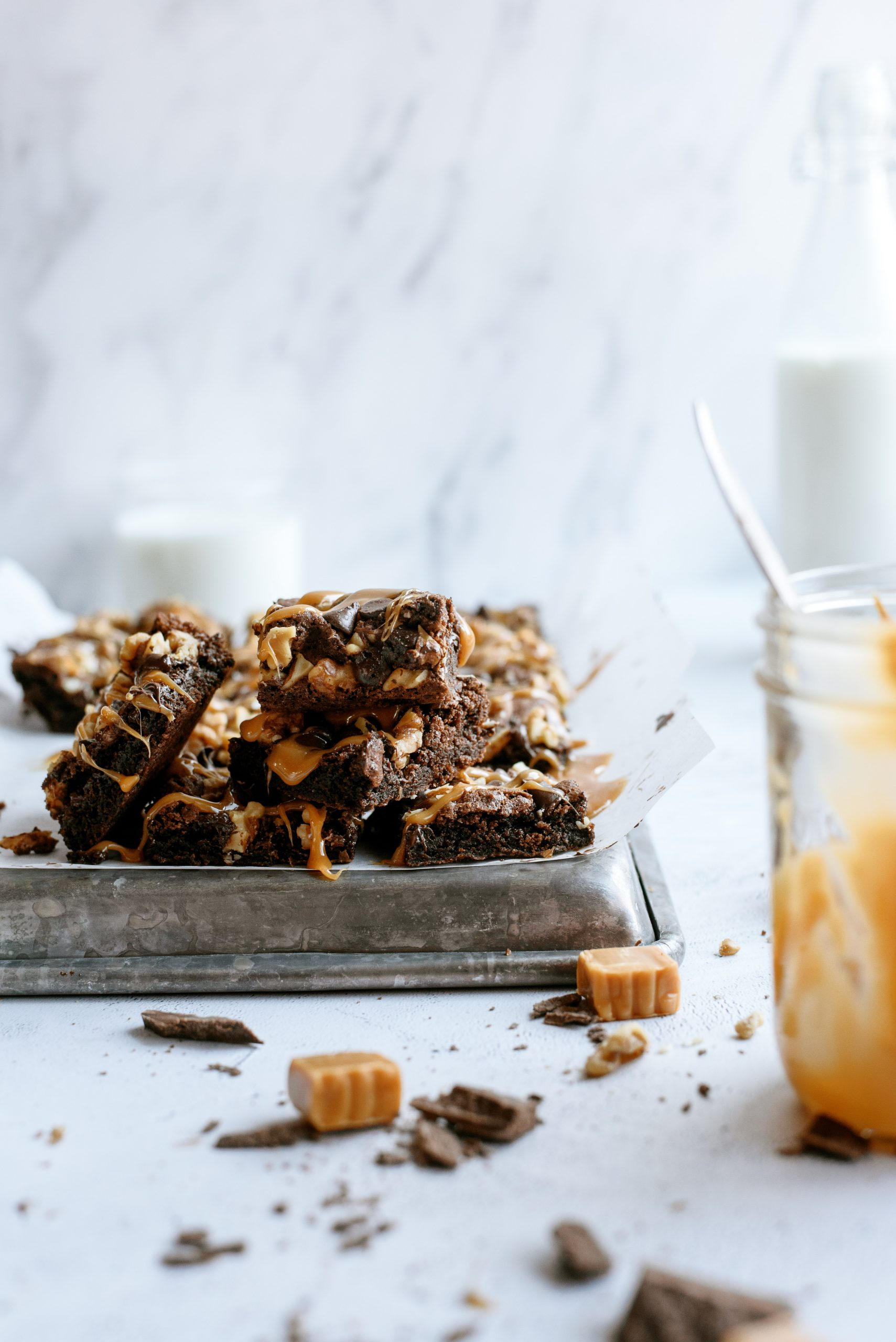 Chocolate Turtle Brownies on a pan with caramel and chocolate shavings