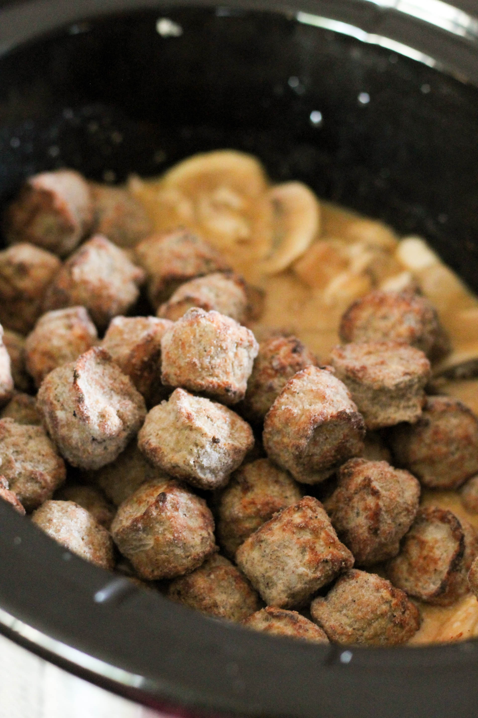 Frozen meatballs added to slow cooker.