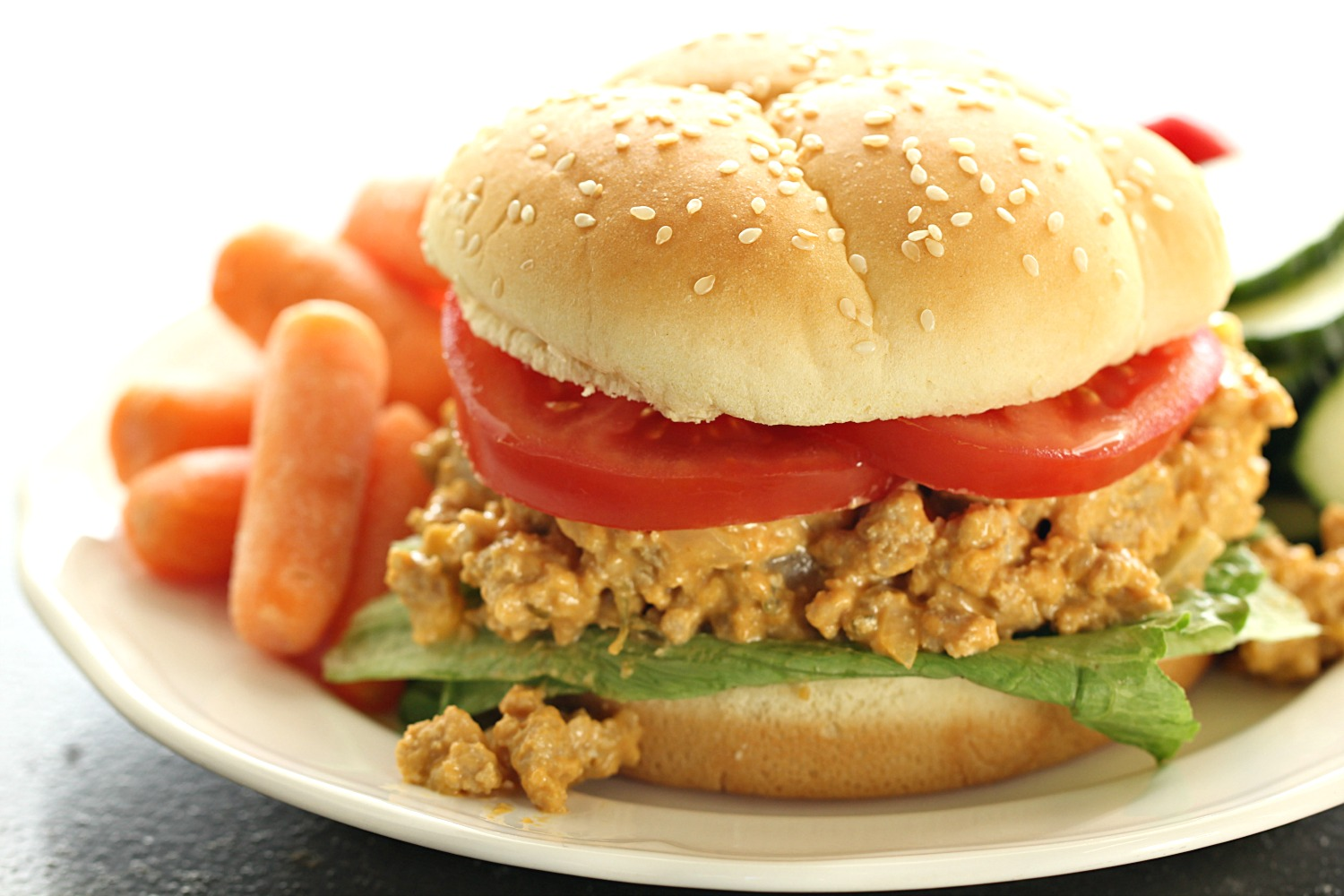 Slow Cooker Cheesy Turkey Burger Joes on a bun plated with vegetables