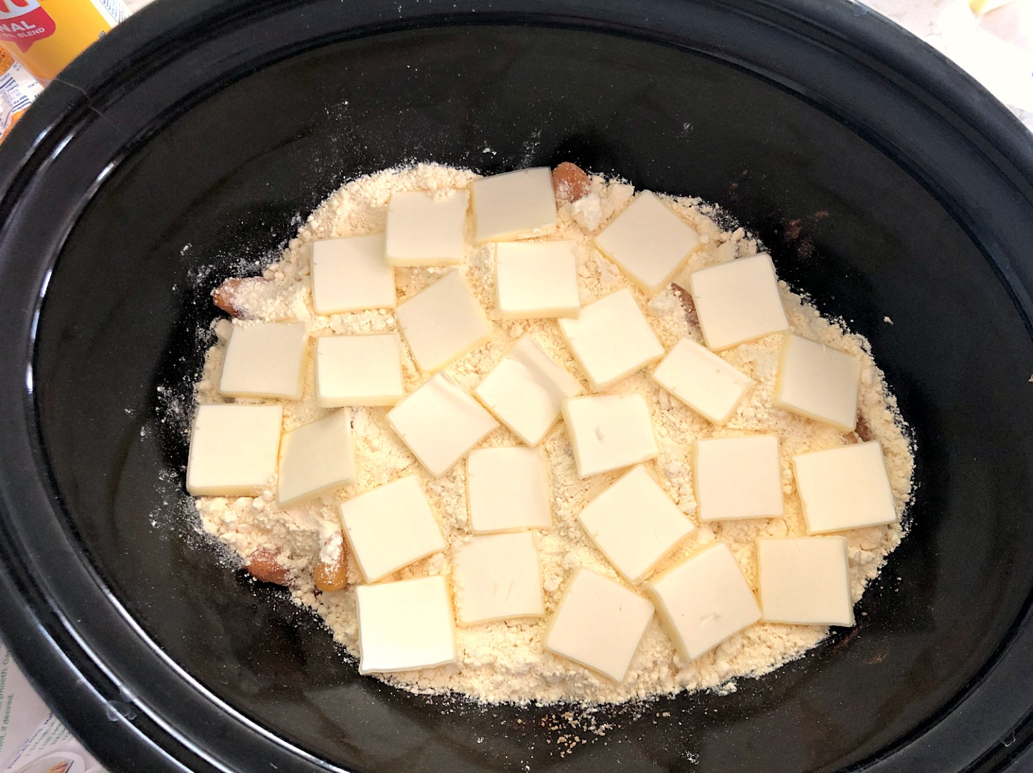 Unbaked Peach Cobbler in the crock pot topped with butter slices