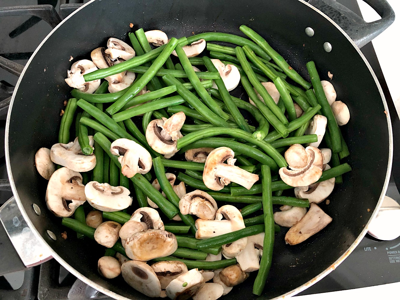 Green beans and mushrooms in a large stir fry pan
