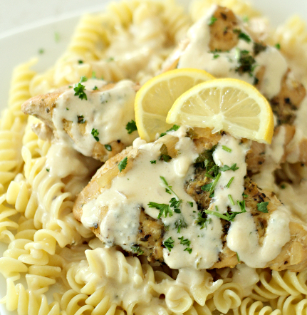 chicken over pasta topped with creamy lemon sauce and lemon slices