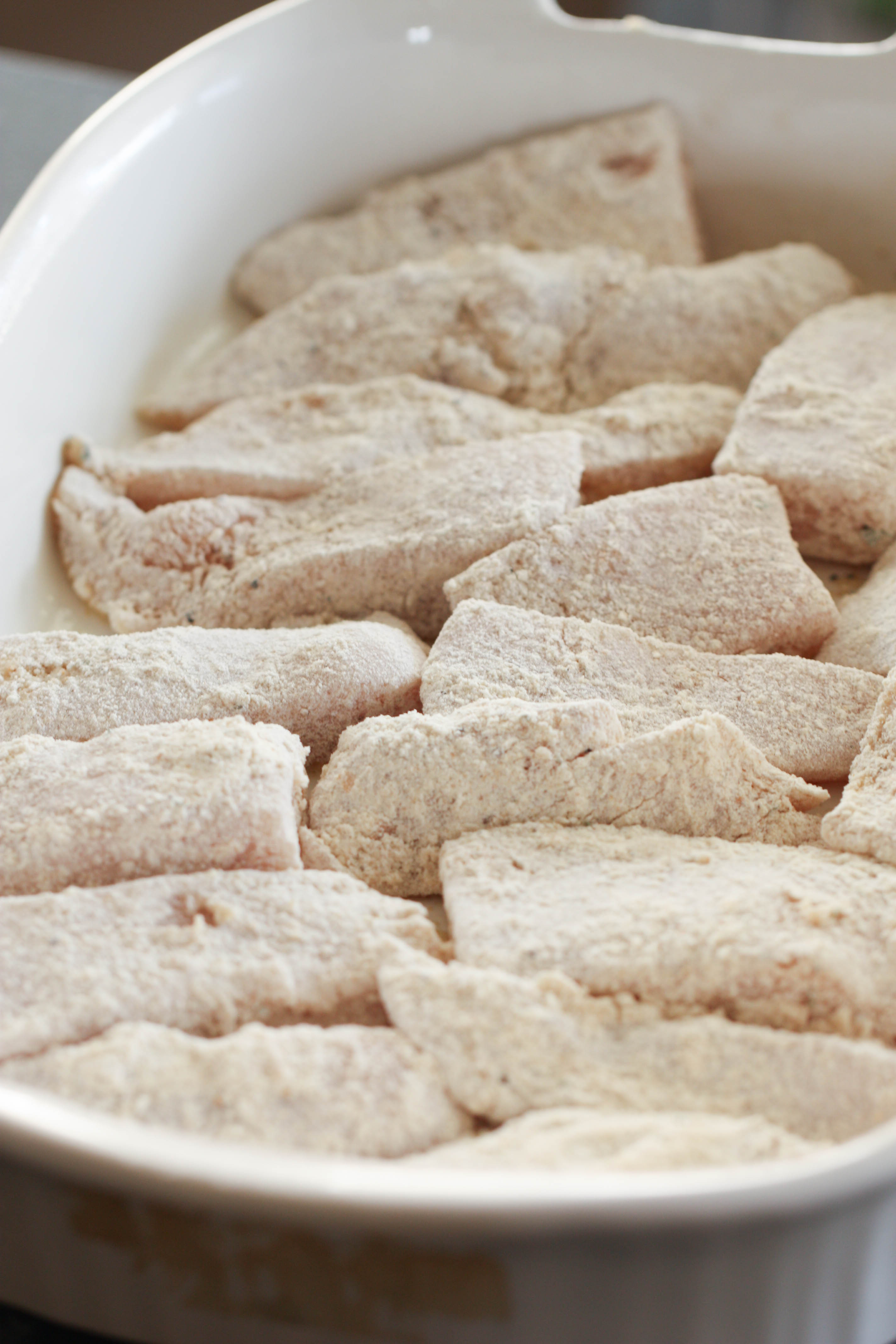 chicken tenders dredged in flour in a white bowl