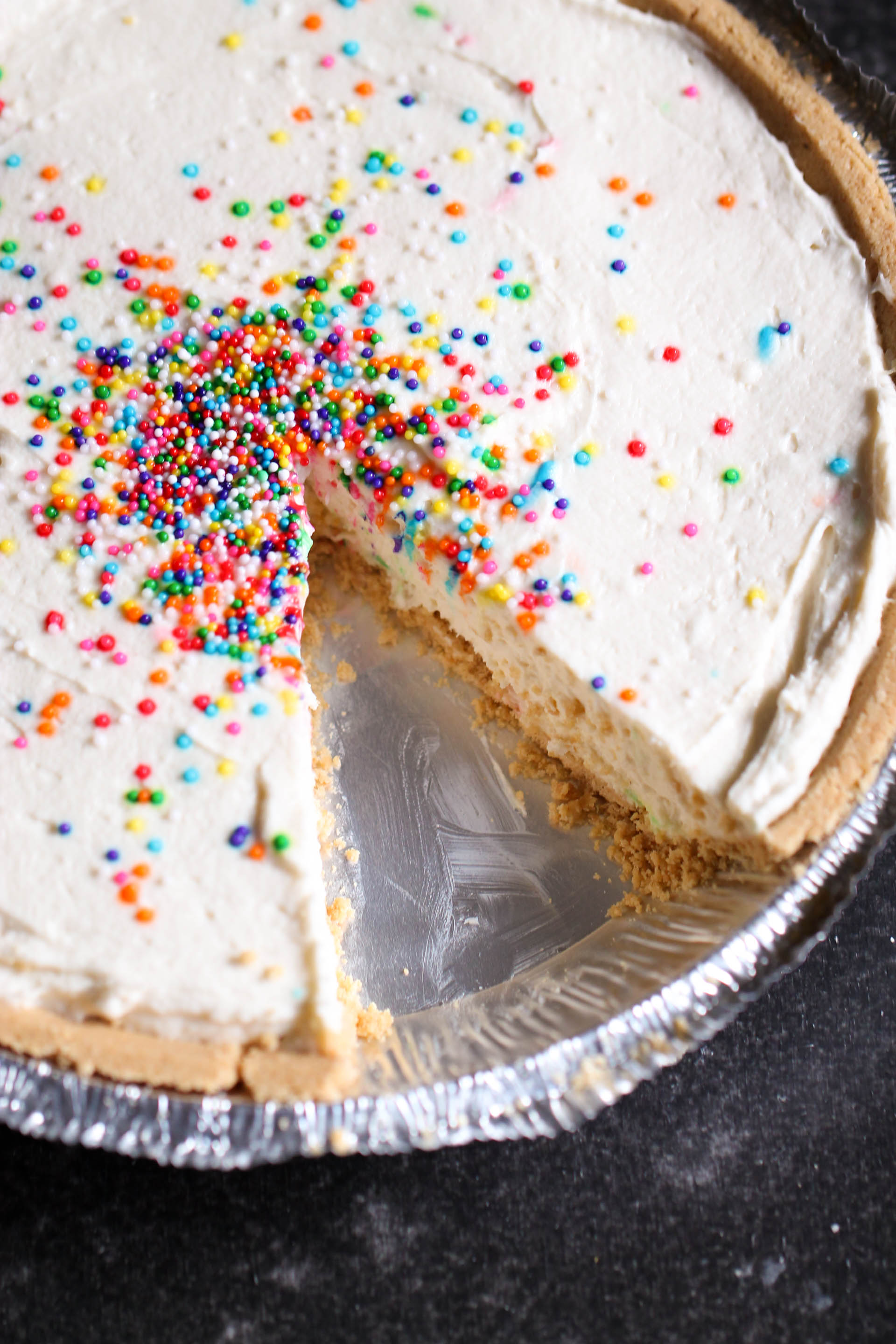 5-Ingredient Cake Batter Cheesecake with sprinkles missing a piece
