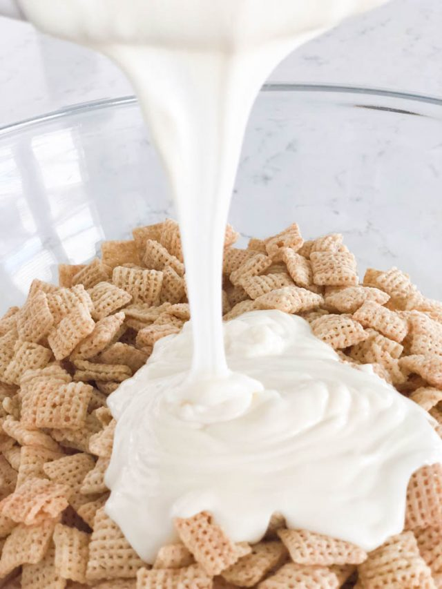 melted white chocolate being poured on cinnamon chex mix