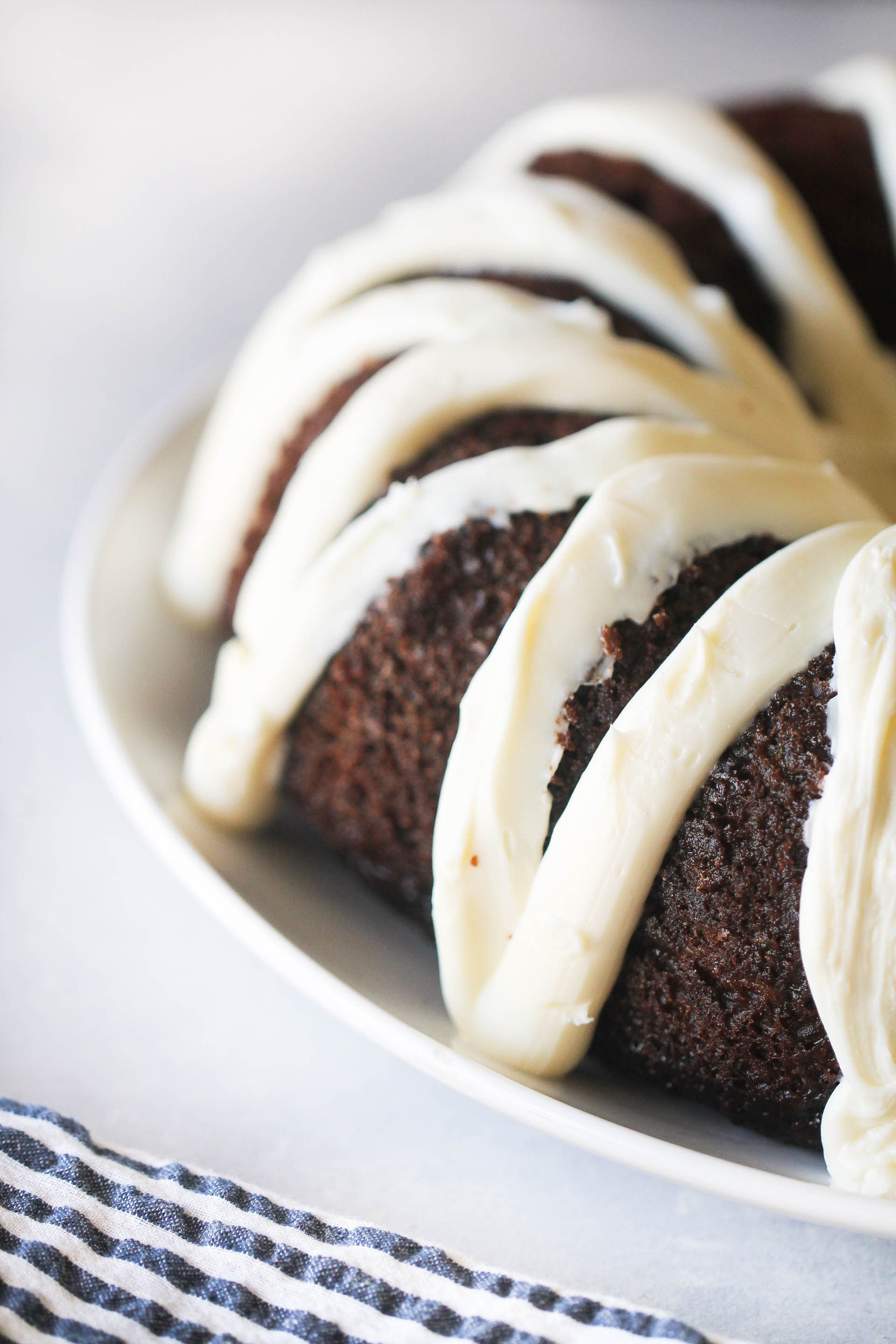 Chocolate Zucchini Cake topped with frosting on a serving platter