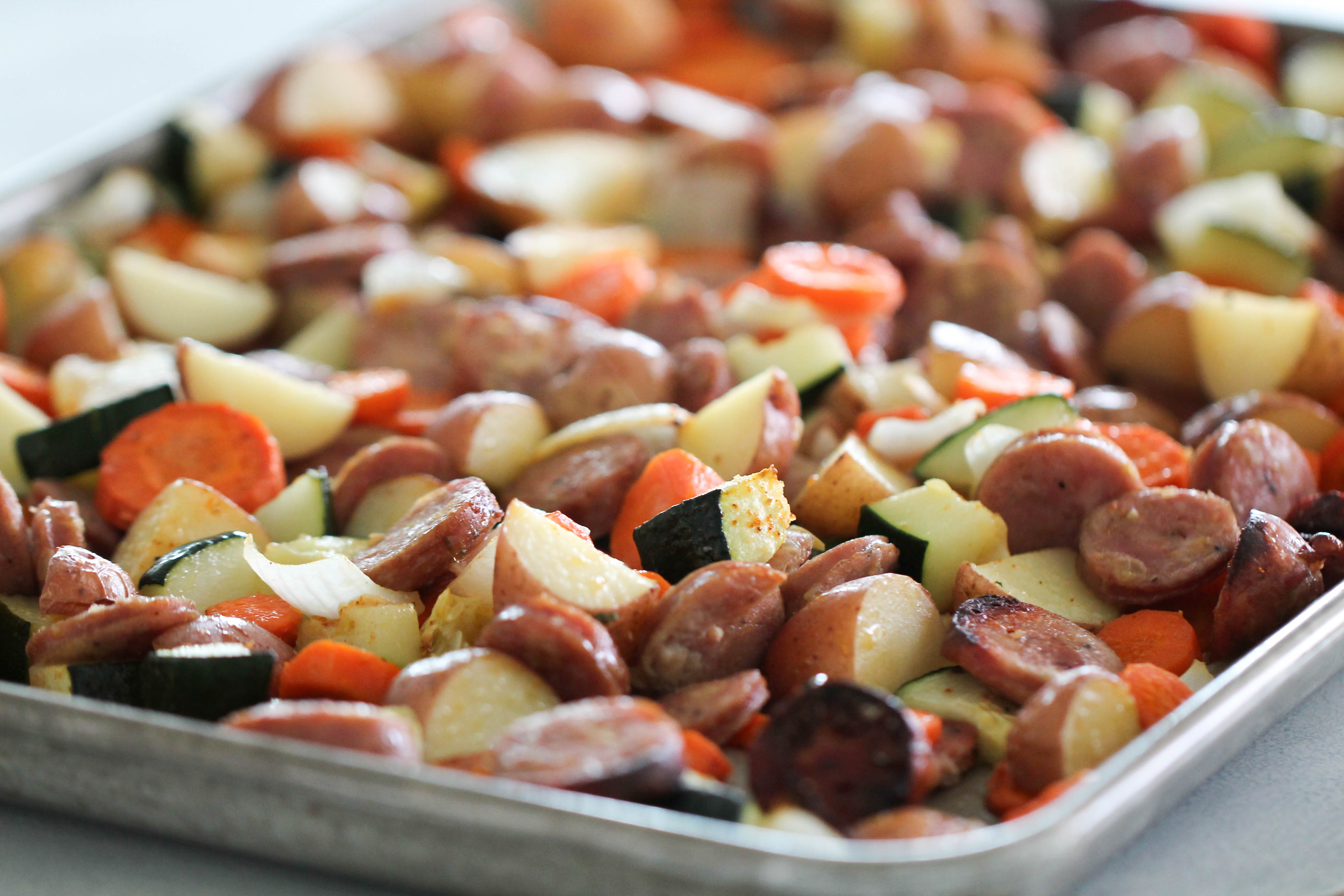 Full view of sausage and vegetables cooked in pan.