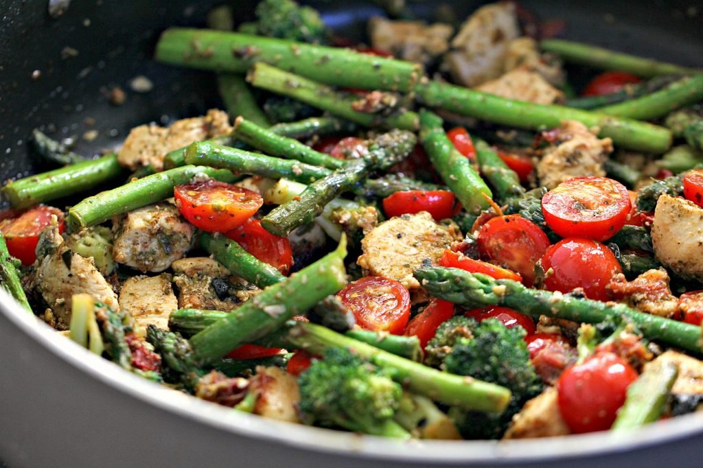 chicken, asparagus, tomatoes, and broccoli mixed together with pesto in a skillet