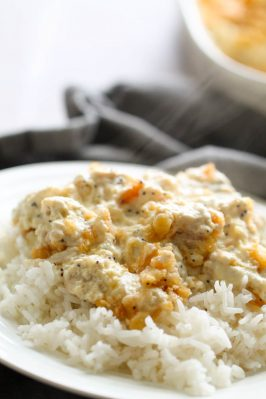 poppy seed chicken casserole served over rice on a plate