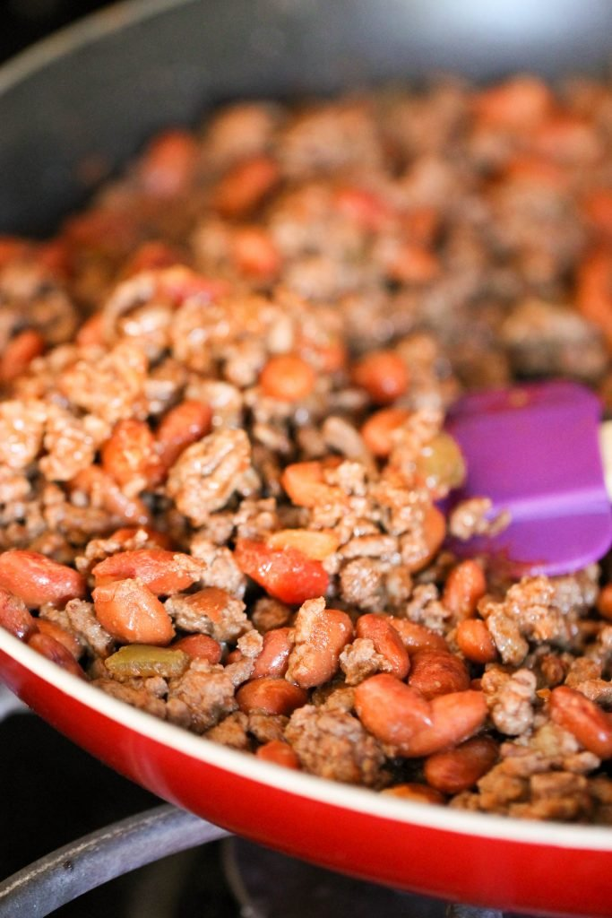 ground beef and beans cooking in a large skillet with purple spatula