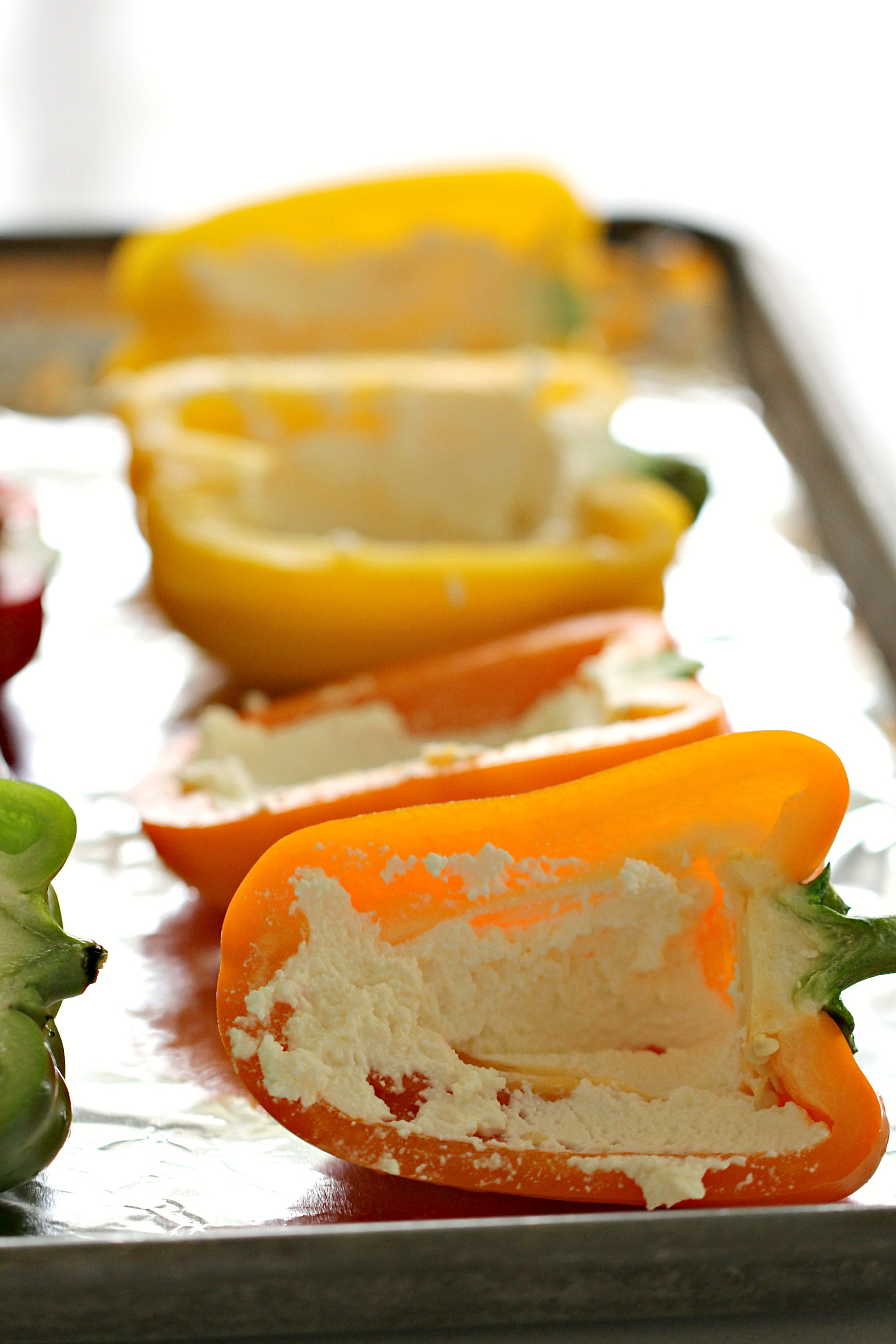 Bell Peppers with ricotta cheese on a baking sheet.