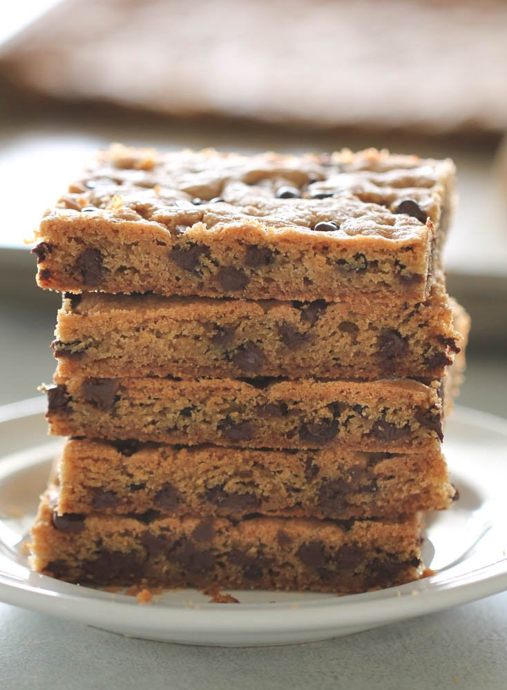 Sliced Sheet Pan Chocolate Chip Cookie Bars stacked on a white plate