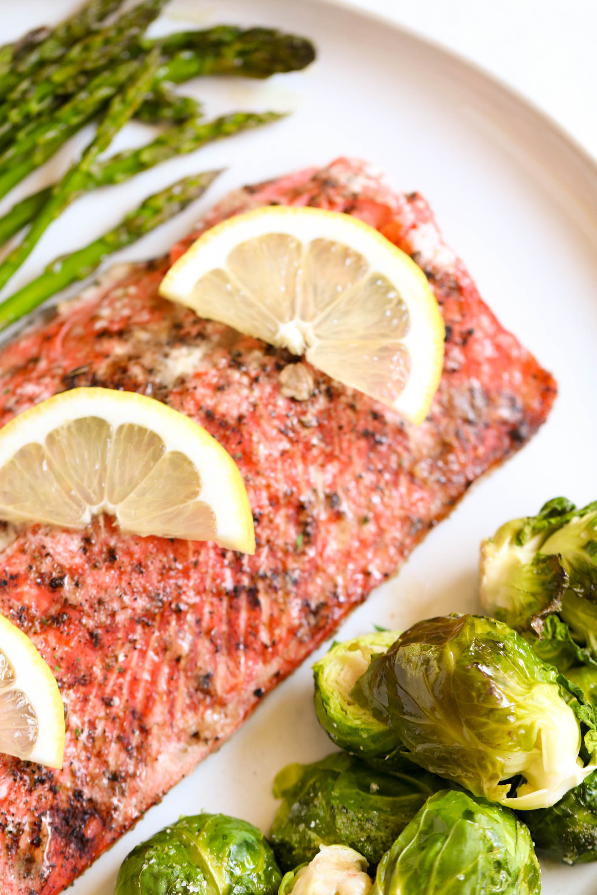 Baked salmon topped with lemons on a pan with brussels sprouts and asparagus
