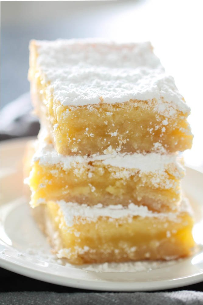 Lemon Bars stacked on plate with powdered sugar